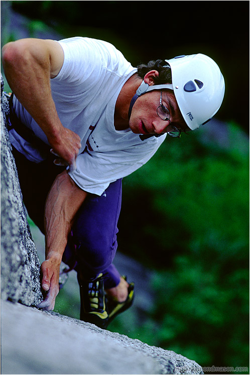 Bruce on Planet Caravan: Squamish, BC, Canada (2002) - Climbing photo of a climber scaling a granite slab, high above the shaded forest floor
