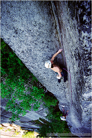 Climbing photo of a climber scaling a thin crack in a large, intimidating corner, high above the ground