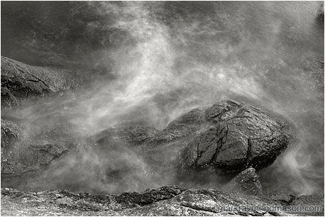 Abstract black and white photograph of misty water crashing over rough, luminescent grey rocks