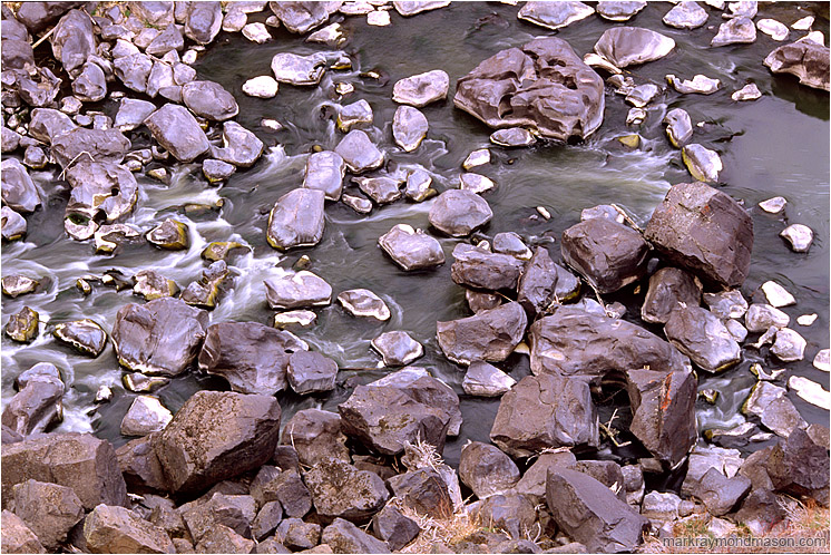 Coloured Rocks, River, Dry Grass: Smith Rocks, OR, USA (2005) - Fine art photograph showing water flowing around river rocks at the bottom of a basalt canyon