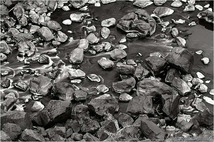 Coloured Rocks, River, Dry Grass (B&W): Smith Rocks, OR, USA (2005-00-00) - Fine art black and white photograph of grey, white and black rocks at the bottom of a river canyon