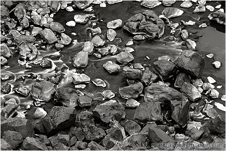 Fine art black and white photograph of grey, white and black rocks at the bottom of a river canyon