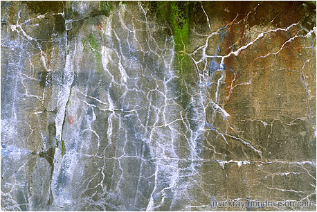 Abstract photograph showing graffiti and patterned cracks in concrete wall