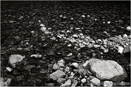 Fine art black and white photograph of pale and dark rocks in a flat, calm river