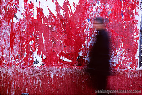 Abstract photo of a red wall and a blurry walking man with an accusing stare