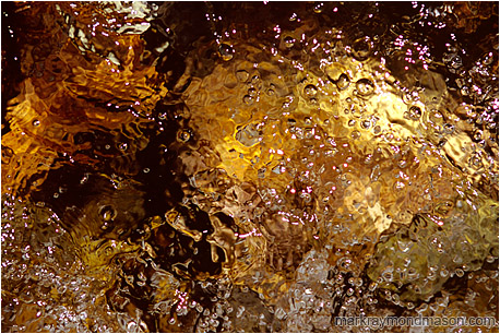 Abstract photograph of highlights and bubbles in a colourful flowing mountain creek