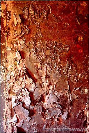 Abstract fine art photograph of a burnt, blistered wall inside a fire-damaged house
