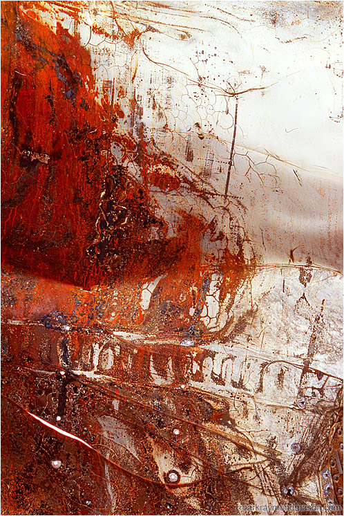Folded Sheet Metal: Near Baker, CA, USA (2008) - Fine art photograph of white paint and red rust on the surface of a folded, puntured piece of sheet metal