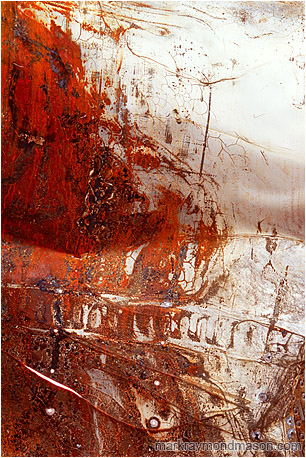 Fine art photograph of white paint and red rust on the surface of a folded, puntured piece of sheet metal