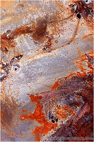Fine art photograph of brushings, chipping paint, and swirling scratches on the surface of a piece of twisted sheet metal