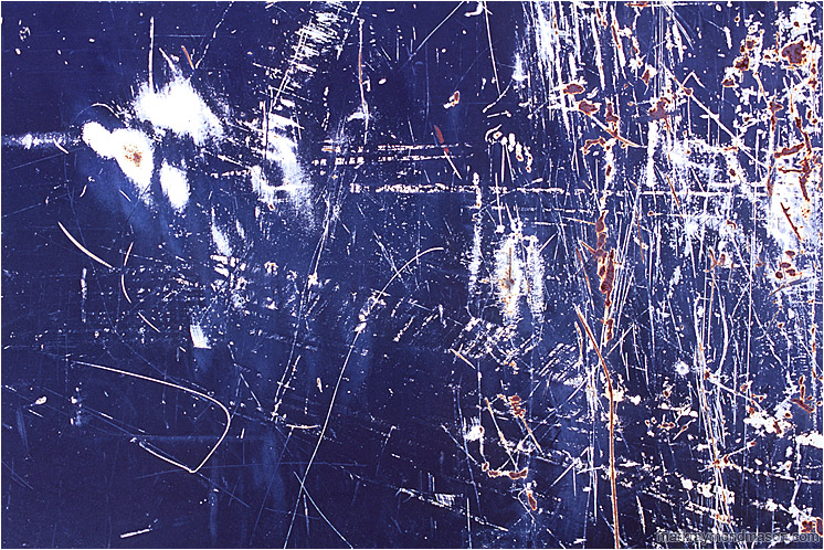 Primer, Paint, Rust: Calgary, AB, Canada (2008) - Abstract photograph of chaotic white and rusty scratches on the surface of a dark blue painted piece of scrap metal
