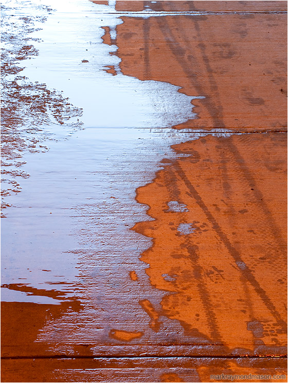 Meltwater, Concrete: Calgary, AB, Canada (2010-02-28) - Abstract photo of a red concrete walkway covered in ice, water and tire tracks