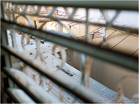 Abstract photograph of blurred window bars guarding an abandoned courtyard between aging concrete buildings