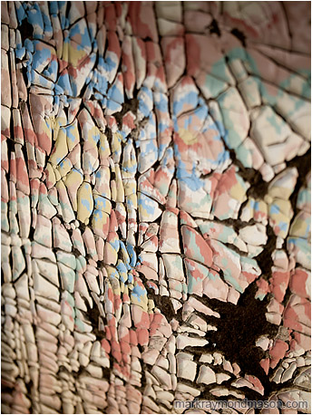Abstract macro photograph showing crumbled paint and shadows on the side of an old woodshed
