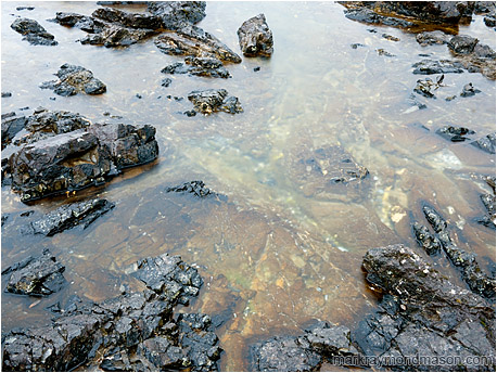 Fine art photograph of sharp black rocks scattered around a colourful tide pool