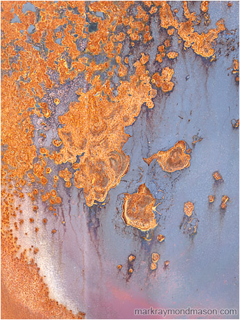 Abstract photograph of swirled red rust on the surface of a bluish painted metal plate