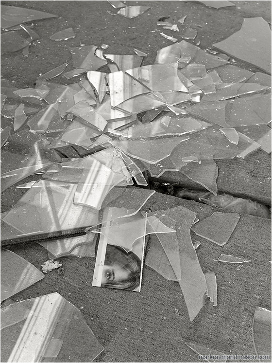 Eyes, Shattered Glass (B&W): Bombay Beach, CA, USA (2011-12-29) - Fine art B&W photo showing a magazine clipping in a pile of shattered window glass