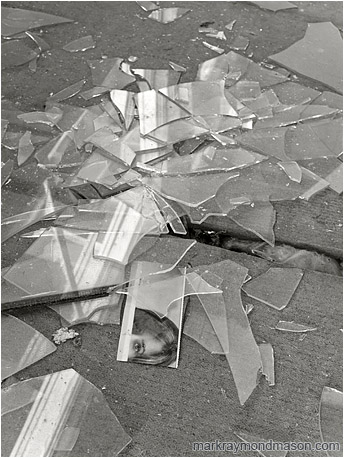 Fine art B&W photo showing a magazine clipping in a pile of shattered window glass