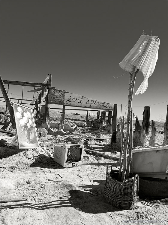 Evil Spirits (B&W): Salton Sea, CA, USA (2012-01-01) - Fine art B&W photograph showing the remains of a structure and scattered objects on a salt flat