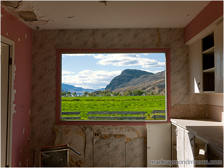Fine art photograph of a window in a derelict house with missing glass but a beautiful pastoral and mountain view