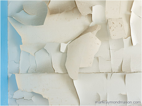 Abstract photograph of light reflecting from blue trim and spilling onto layered tiles of dirty white paint