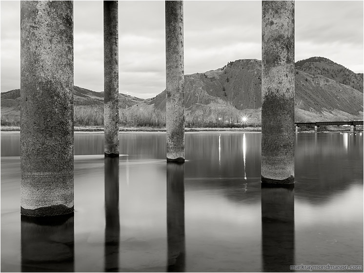 Concrete Piles, Rushing Water: Kamloops, BC, Canada (2012) - Fine art black and white photograph of large piles rising out of the frame from the smooth water of a full river