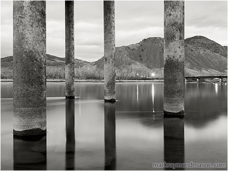 Fine art black and white photograph of large piles rising out of the frame from the smooth water of a full river