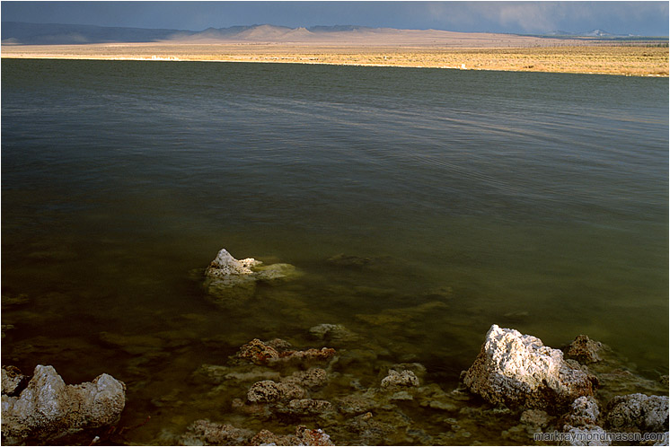Lake Rocks, Arching Horizon: Mono Lake, CA, USA (2002-00-00) - Fine art photograph of small volcanic rocks in a large lake, with stormclouds and sunshine in the distance