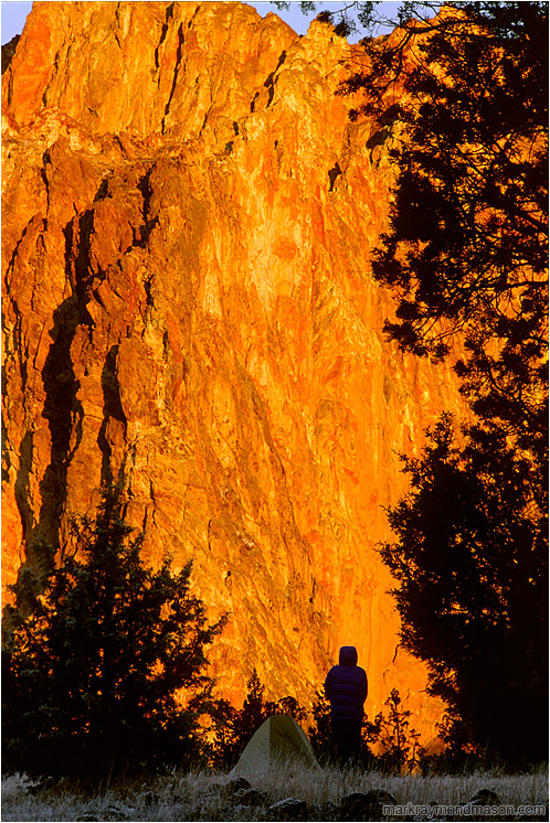 Terri, Tent, Orange Rock Sunrise: Smith Rocks, OR, USA (2002-00-00) - Lifestyle photo of a silhouetted woman and her tent, in front of a wall of bright orange, sunlit rock