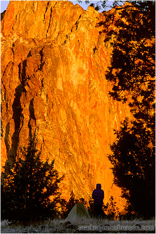 Lifestyle photo of a silhouetted woman and her tent, in front of a wall of bright orange, sunlit rock