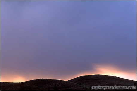 Fine art photograph of storm clouds over the hills at sunset