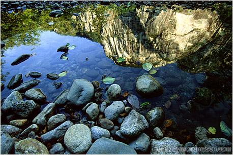Abstract photograph showing reflections of cliffs and river rocks in calm water