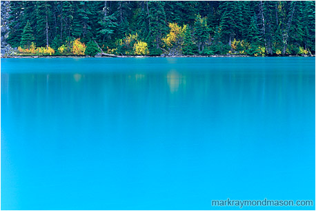 Fine art photograph of blue water, reflections, and fall colors