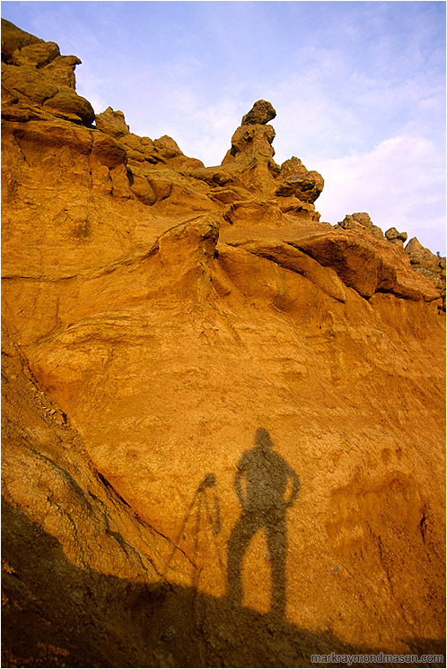 Self Portrait With Camera Shadow: Near Kamloops, BC, Canada (2002-00-00) - Landscape photograph of a silhouetted photographer and camera mounted tripod against a dramatic sculpted hoodoo background
