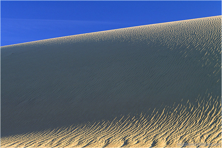 Dune, Shadows: Death Valley, CA, USA (2003) - Abstract nature photograph of shadows in a sand dune and pale blue sky