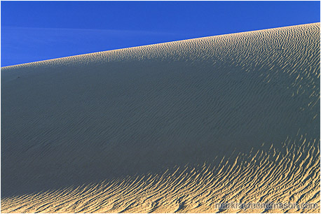 Abstract nature photograph of shadows in a sand dune and pale blue sky