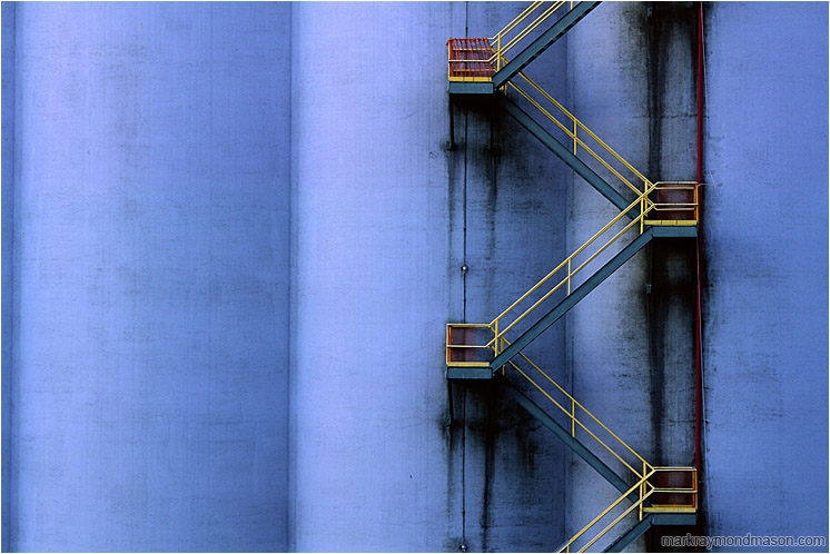 Silo, Stairs: Vancouver, BC, Canada (2004-00-00) - Abstract photograph showing a yellow fire escape winding down a huge grain silo