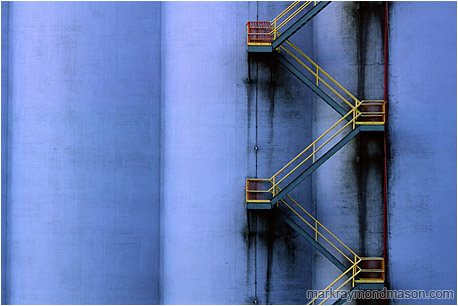 Abstract photograph showing a yellow fire escape winding down a huge grain silo