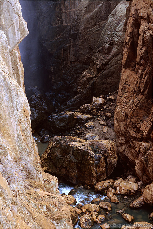 River Canyon, Mist: Near El Chorro, Spain (2006) - Fine art nature photograph of water and mist in a deep slot canyon, with steep cliffs of orange and black rock