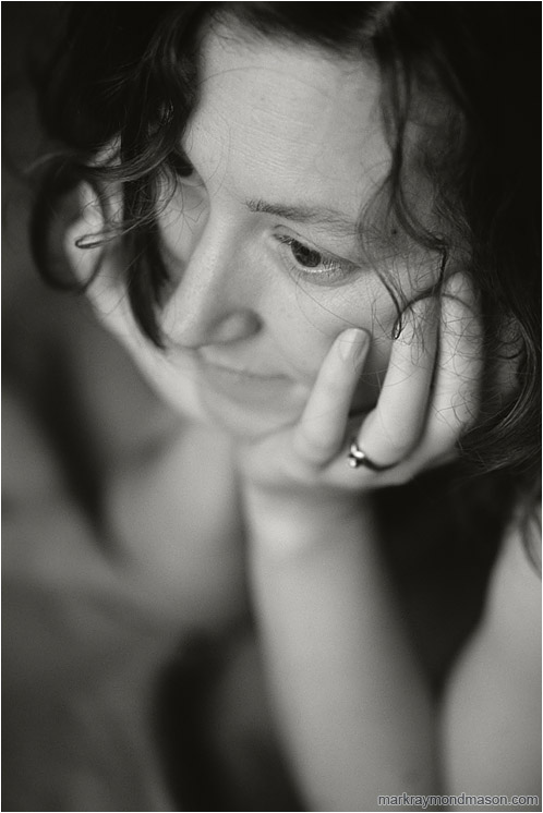 Terri, Daydreaming (B&W): Calgary, AB, Canada (2008) - Fine art black and white photograph of a beautiful woman with her head in her hands and curled hair on her face