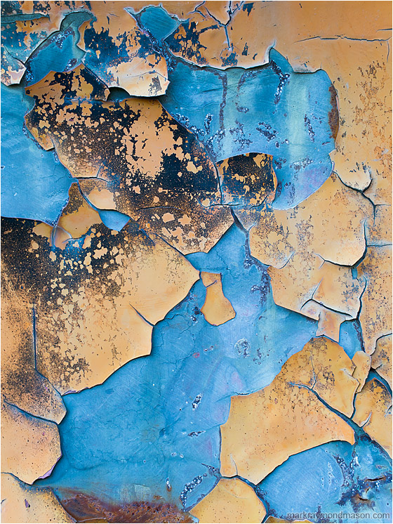 Cracking Sky, Pale Blue: Near Kamloops, BC, Canada (2013-07-06) - Abstract macro photograph showing large chunks of peeling orange paint falling away to reveal cool, blue-tinted metal beneath