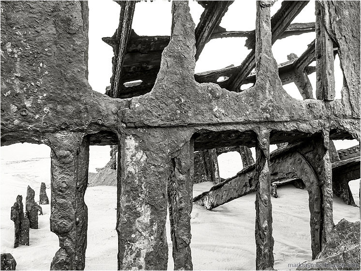 Shipwreck, Flowing Sand: Near Astoria, OR, USA (2015) - Fine art black and white photograph of the metal skeleton of an old wrecked ship, surrounded by pale, ocean-worn sand.
