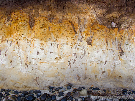Fine art photograph of orange and red patina over a compact mud seaside cliff