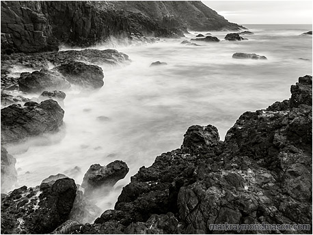 Fine art black and white long exposure photograph of waves crashing on a rugged bay