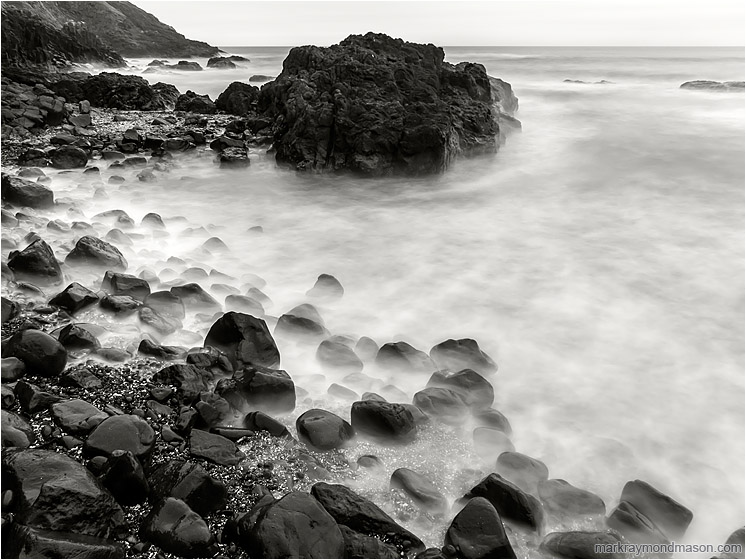 Worn Rocks, Crashing Waves: Near Stawberry Hill Park, OR, USA (2015-10-21) - Fine art black and white photograph of smokey waves swirling around a rocky knob and a bounder-strewn beach