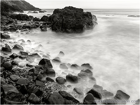Fine art black and white photograph of smokey waves swirling around a rocky knob and a bounder-strewn beach
