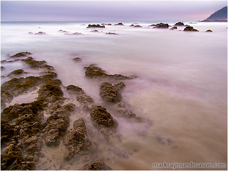 Fine art long-exposure photograph of barnacled rocks and clouds of sand as seawater washes over a tidepool