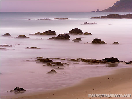 Fine art landscape photograph of misty water around rocky islands in the last light of a coastal evening