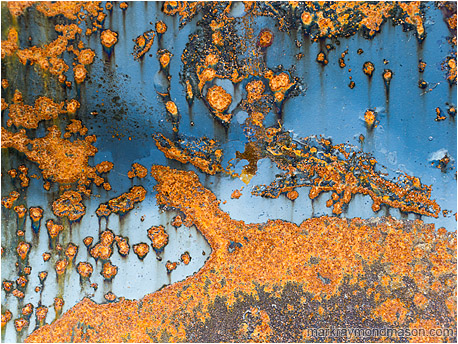 Abstract fine art photograph of red rusted spots looking like islands in an sky-blue sea of paint