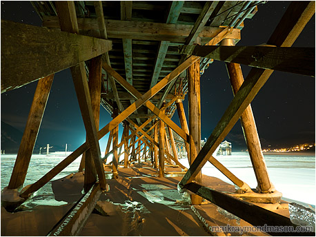 Fine art photograph showing giant beams on the underside of a wharf, frozen in ice, set against a night sky with faint stars